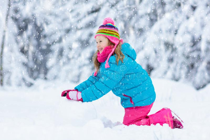 Child making snowman. Kids play in snow in winter. Kid making snowman in snowy winter park. Children play in snow. Little girl in colorful jacket and hat stock image