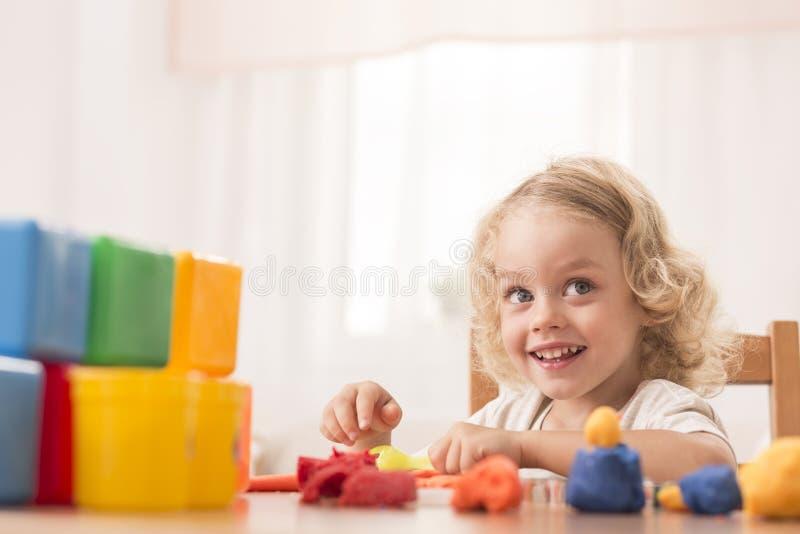 Child making toys using plasticine royalty free stock photography