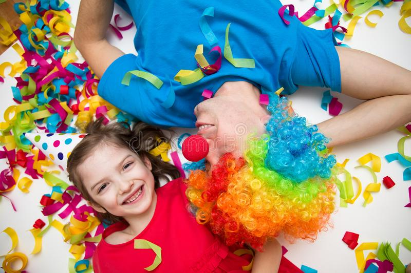 A child and a man in a clown wig lie in confetti on a white background. Celebrate a bright event. royalty free stock images