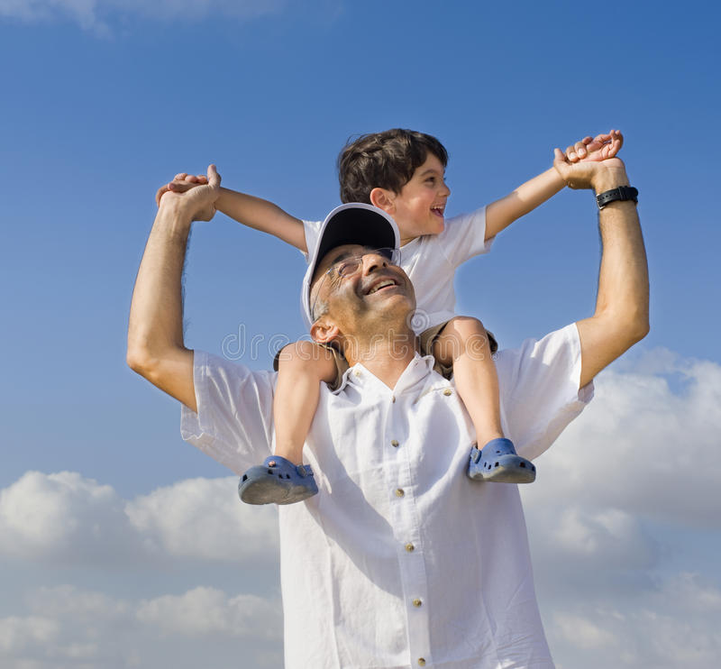 Child on man shoulders stock image