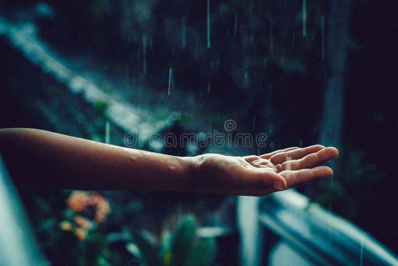 Child& x27; mano de s debajo de la lluvia imagenes de archivo