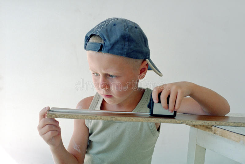 Child measuring wooden plank royalty free stock photos