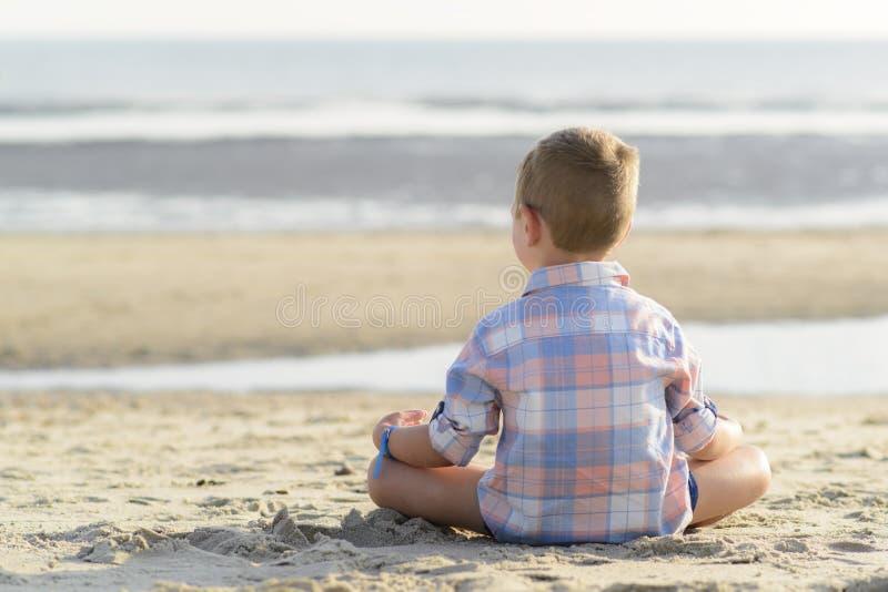 Child meditating on the beach stock photo