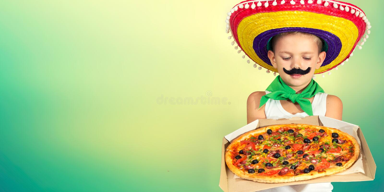 A child in a Mexican sombrero eats pizza. stock images