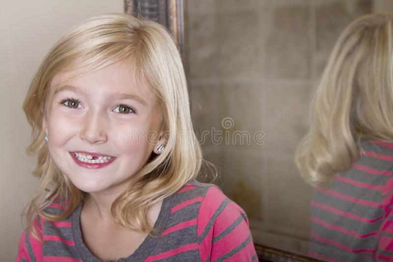 Child missing front tooth. Close up of child missing her top front tooth stock image