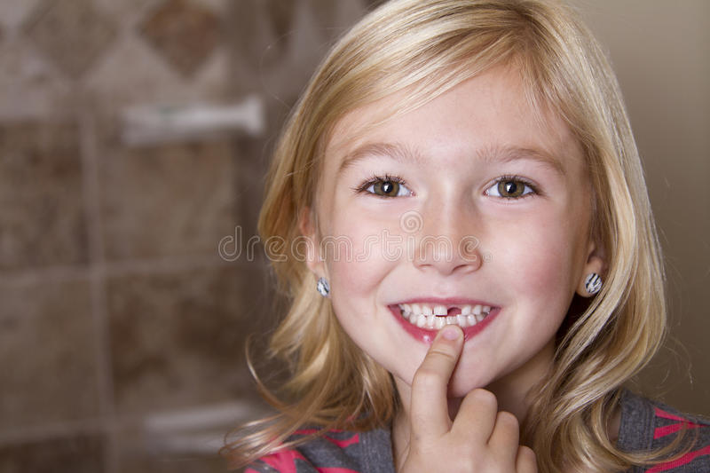 Child missing front tooth. Pointing at it with her finger royalty free stock photography