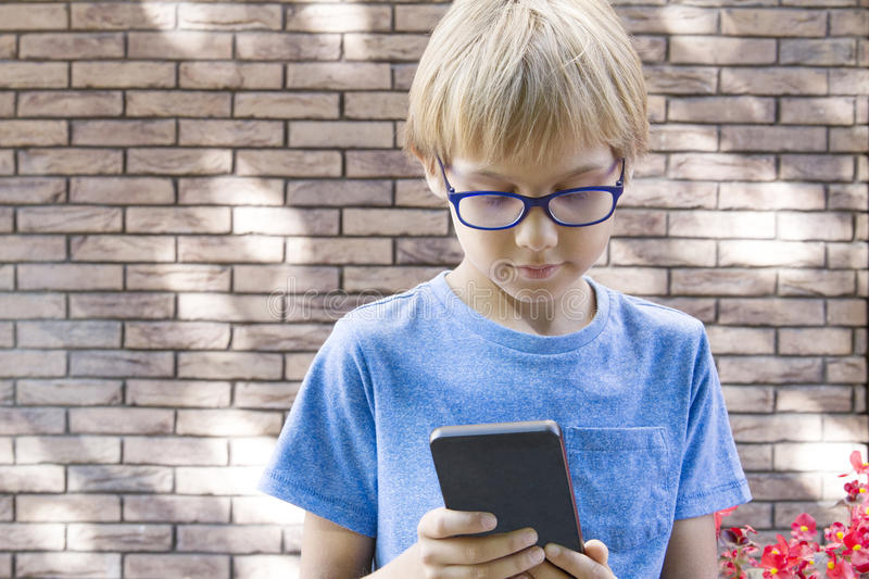 Child with mobile phone outdoors. Boy looks at the screen, use application, plays. City background. School, people stock image