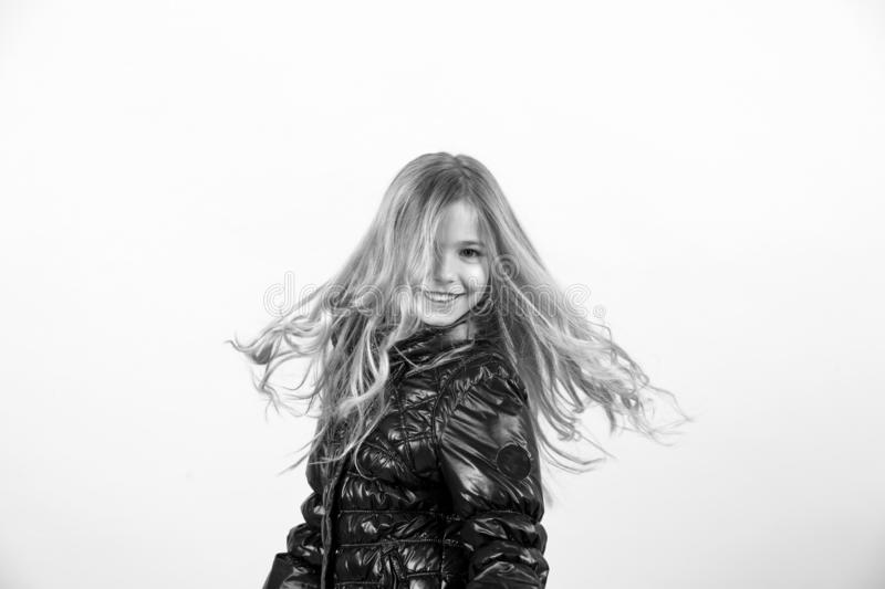 Child model shake long blond hair. Fashion, autumn style, trend. Happy childhood concept. Girl in black coat smile on orange background. Kid beauty, look stock image
