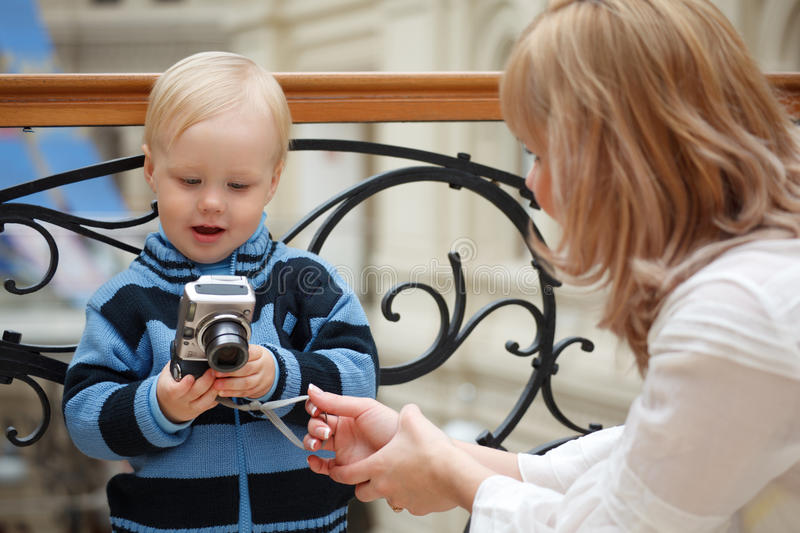 Child And Mother. Boy Examines Photo With Camera Stock Image
