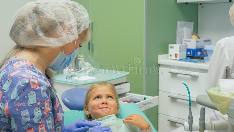 Child with a mother at a dentist`s reception. The girl lies in the chair, behind her mother. The doctor works with an. Assistant. Procedure for drilling a tooth stock photos