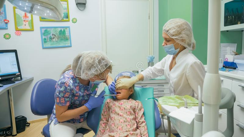 Child with a mother at a dentist`s reception. The girl lies in the chair, behind her mother. The doctor works with an. Assistant. Procedure for drilling a tooth stock image