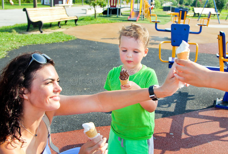 Child and mother eating ice cream outdoors in summer park. Mother, son and daughter enjoying vacation stock photo