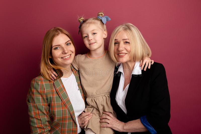 Child with mother and grandmother together smiling and hug isolated. stock photography