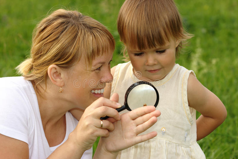Child with mother looking at snail royalty free stock photos