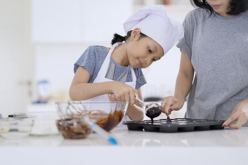 Child and mother preparing chocolate dough royalty free stock photography
