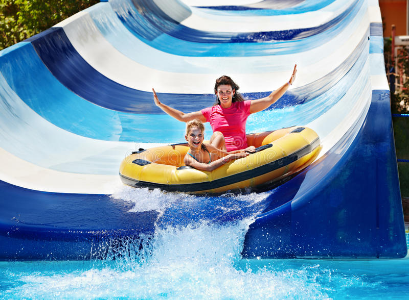 Child with mother on water slide at aquapark. royalty free stock photography
