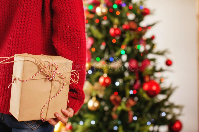 Child near the Christmas tree with a gift behind stock image