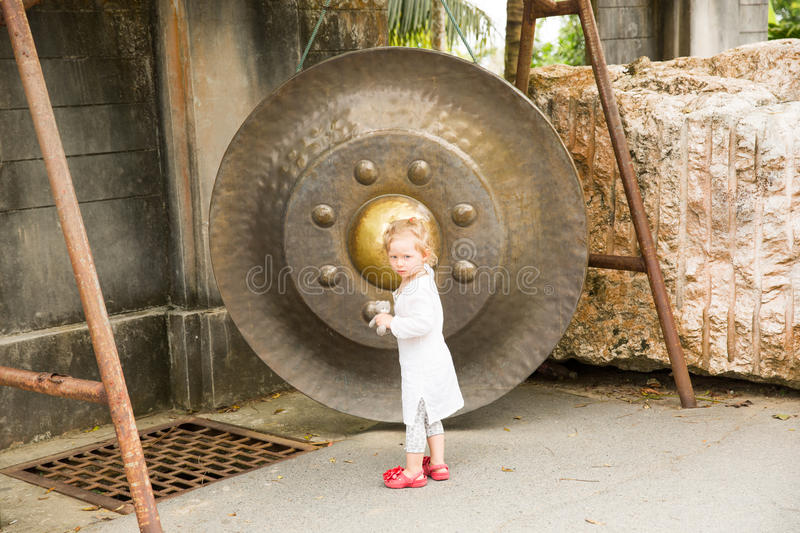 Child near Thai gong in Phuket. Tradition asian bell in Buddhism temple in Thailand. Famous Big bell wish near Gold Buddha royalty free stock photos