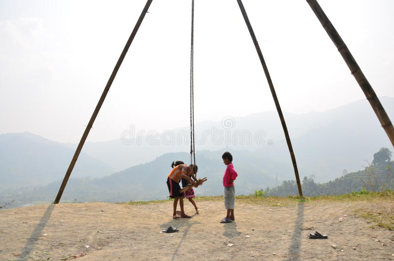 Child nepalese playing swing machine made for bamb stock photos