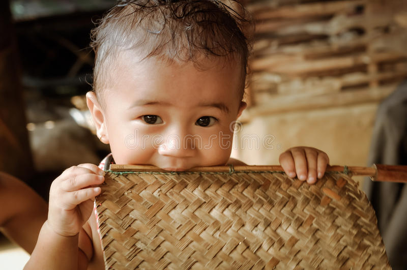 Child at Nepali refugee camp in Nepal. Damak, Nepal - circa May 2012: Photo of small cute boy looking to photocamera and holding wooden stick in his mouth at royalty free stock image