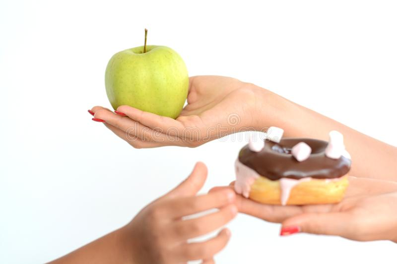 Child obesity concept with little girl hand choosing a sweet and unhealthy doughnut instead of a fruit. Child obesity concept with little kid hand choosing a stock image