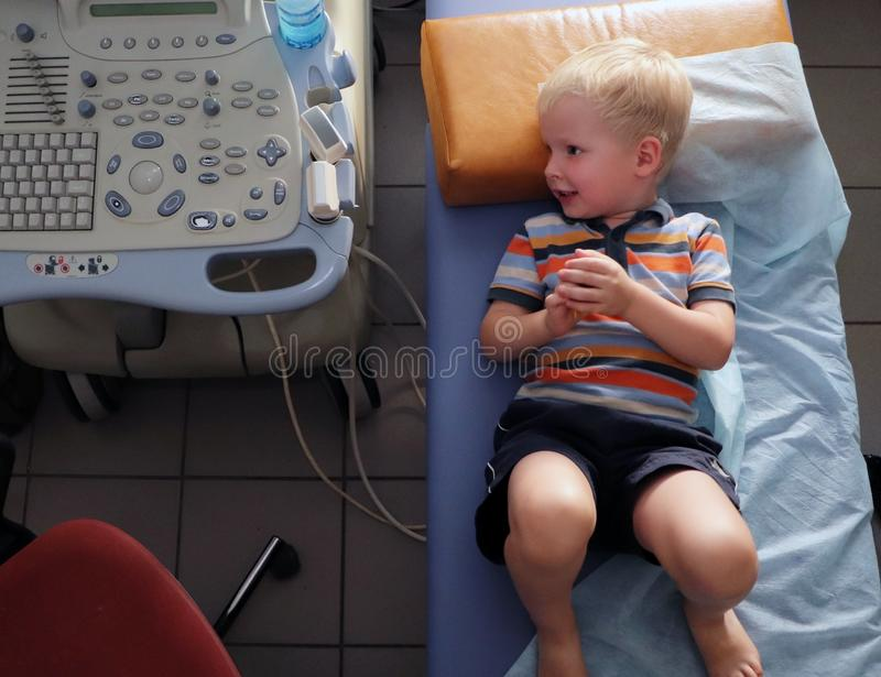 The child in the office of ultrasound. Little boy awaits an ultrasound doctor for examination. Little boy awaits an ultrasound doctor for examination. The child royalty free stock images