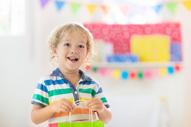 Child opening birthday present. Kid at party stock images