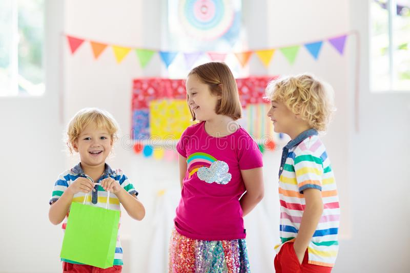 Child opening birthday present. Kid at party stock photography