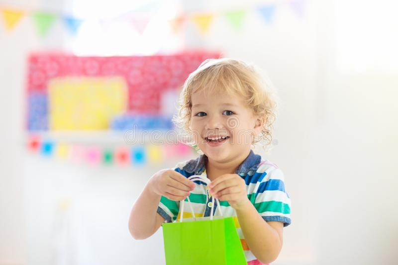 Child opening birthday present. Kid at party royalty free stock image