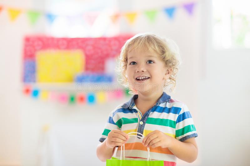 Child opening birthday present. Kid at party royalty free stock photo
