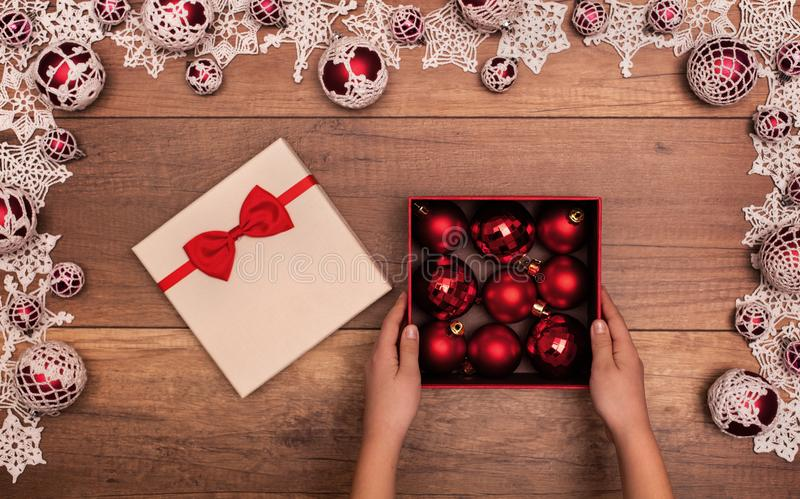 Child opening christmas present with red baubles stock images