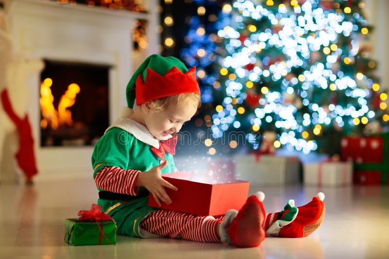 Child opening present at Christmas tree at home. Kid in elf costume with Xmas gifts and toys. Little baby boy with gift box and stock photography