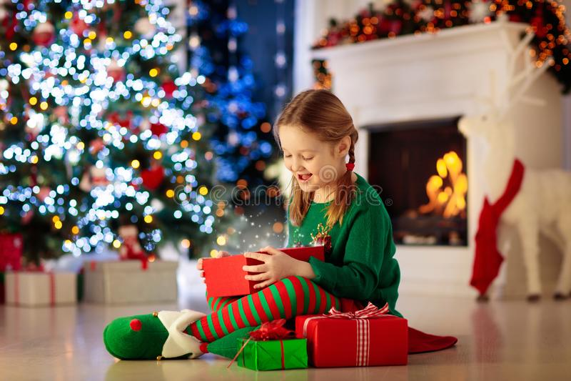Child opening present at Christmas tree at home. Kid in elf costume with Xmas gifts and toys. Little girl with gift box and candy royalty free stock photos