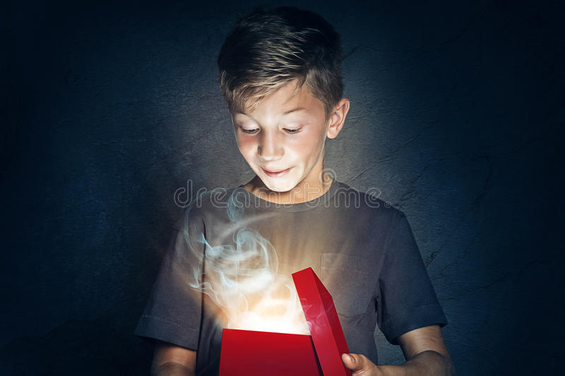 Child opens gift. Boy is surprised when opening a box royalty free stock photo