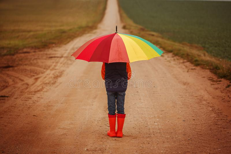 Child in orange rubber boots holding colorful umbrella under rain in autumn. Back view.  stock images