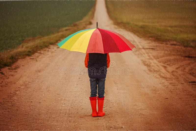 Child in orange rubber boots holding colorful umbrella under rain in autumn. Back view royalty free stock images