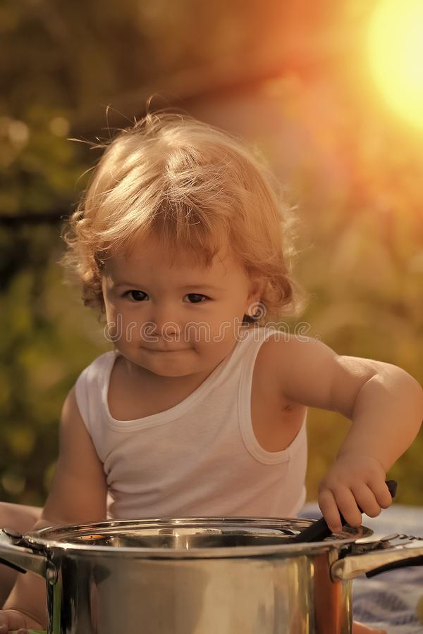 Child outdoor. Portrait of smiling baby boy with blonde curly hair in white underwear holding kitchen utensil royalty free stock images