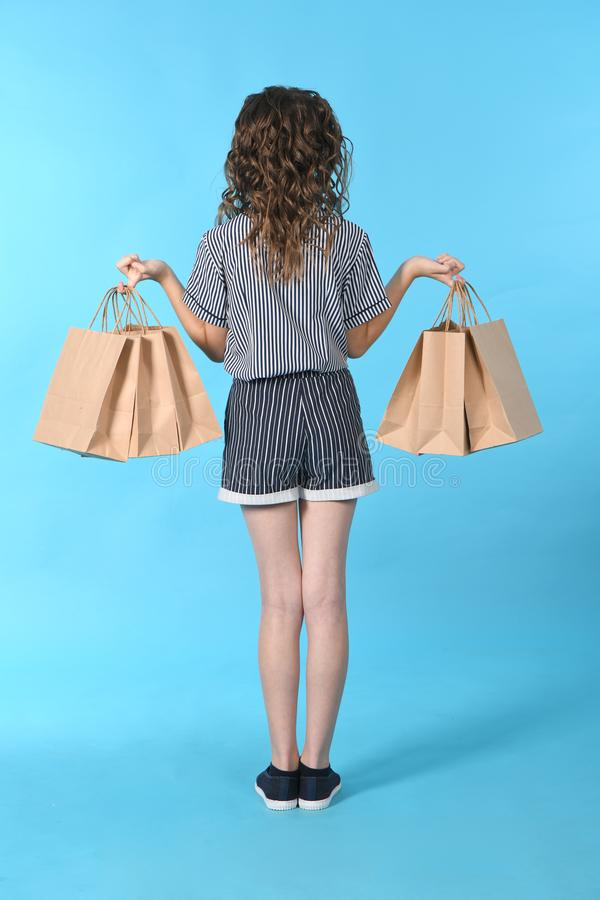 Child with a packet isolated on blue background. Holiday present, shopping. Kid happy shopping in mall stock photography