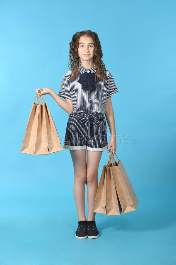 Child with a packet isolated on blue background. Holiday present, shopping. Kid happy shopping in mall stock photo