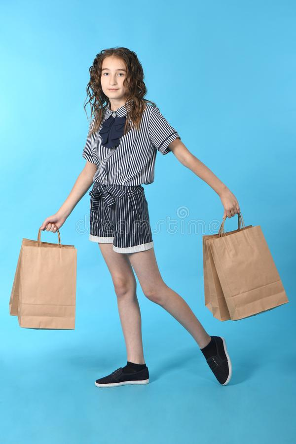 Child with a packet isolated on blue background. Holiday present, shopping. Kid happy shopping in mall stock image