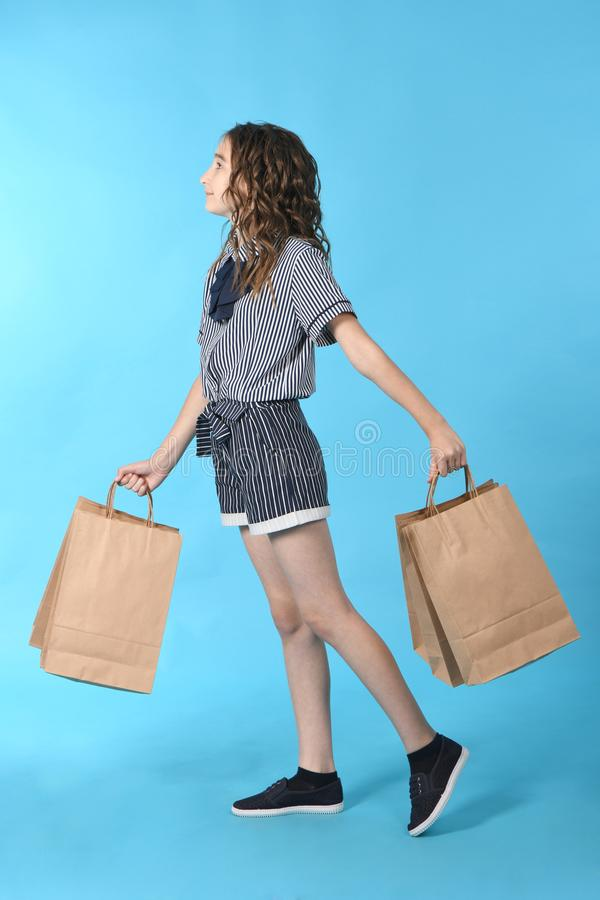 Child with a packet isolated on blue background. Holiday present, shopping. Kid happy shopping in mall stock photos