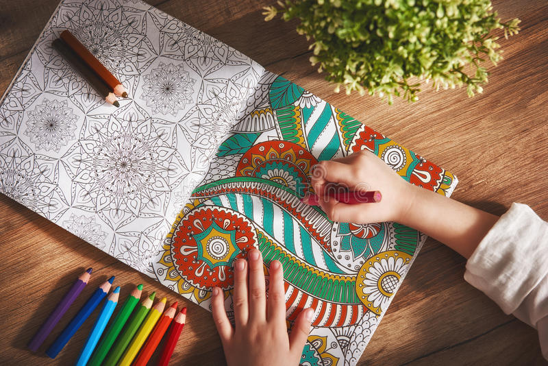 Child paint a coloring book. New stress relieving trend. Concept mindfulness, relaxation royalty free stock image