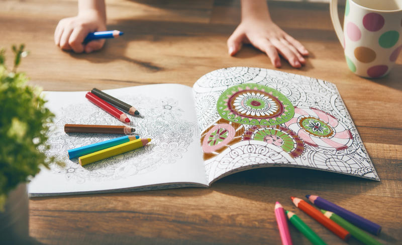 Child paint a coloring book. New stress relieving trend. Concept mindfulness, relaxation royalty free stock photography
