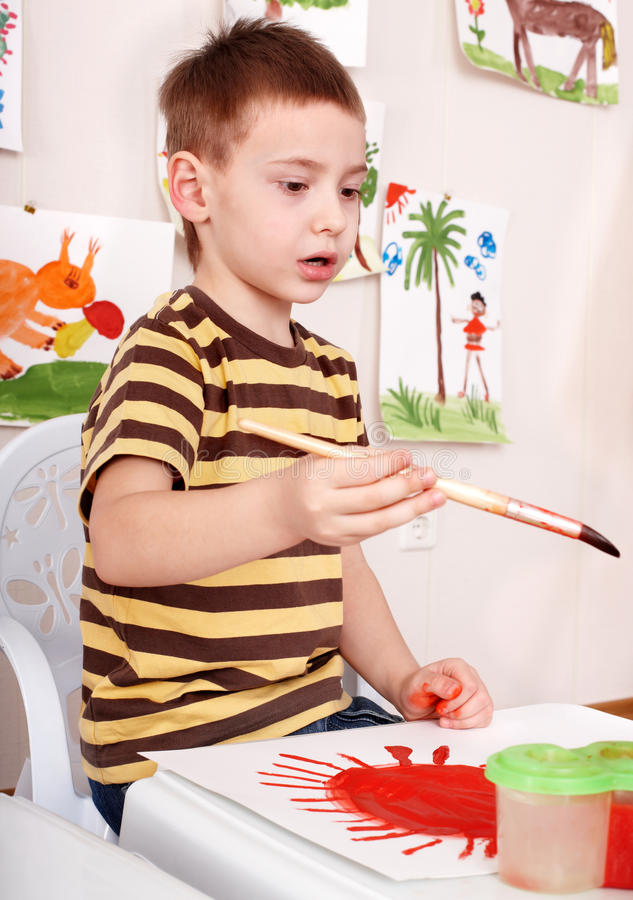 Child paint picture in preschool. royalty free stock images