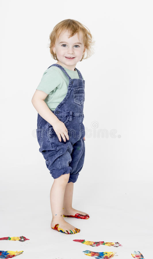 Child with painted feet holding trousers stock image