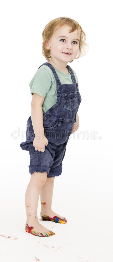 Child with painted feet holding trousers royalty free stock photo