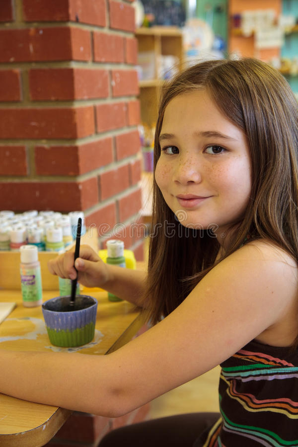 Child painting. A eurasian girl painting a piece of pottery with a paintbrush and water colors at a table royalty free stock image
