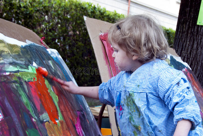 Child painting. A blond caucasian girl child girl painting a picture with a paintbrush and water color stock images