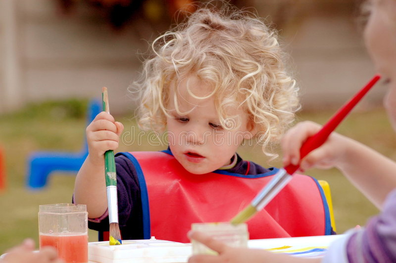 Child painting. A beautiful little caucasian white girl child with long blond curly hair and concentrating expression in the pretty face painting a picture with royalty free stock photos