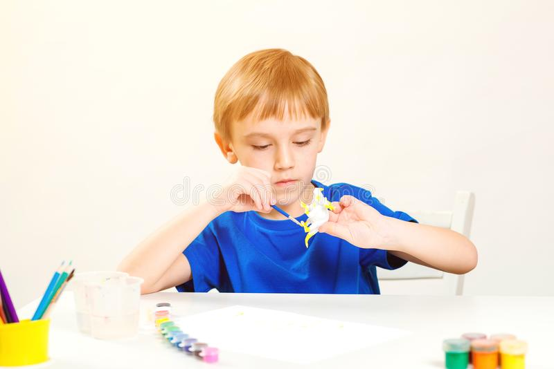 Child painting in art class. Creativity and education concept. Cute little boy paints small figure dinosaur. Children study. Kids. Hobby and creativity stock photos